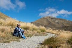 Человек сидя на стороне дороги ждать кто-то Стоковая Фотография RF