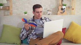 Человек сидя на таблице использует ноутбук и держит протезные insoles в руке сток-видео