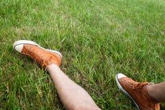 Человек сидя на траве нося оранжевые тапки стоковая фотография rf