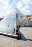 Человек сидя рядом с стеклянной пирамидой жалюзи стоковое изображение