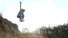 Человек скачет в песок в замедленном движении outdoors на заход солнца акции видеоматериалы