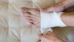 Человек скорой помощи прикладывая повязку для раненой ноги и лодыжки сидя на кресле дома сток-видео