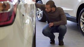 Человек смотрит колесо автомобиля на дилерских полномочиях стоковые изображения rf