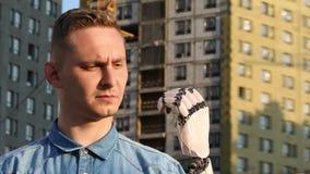 Человек смотрит на его робототехнической руке на фоне зданий под конструкцией, анимацией 3d 4K видеоматериал