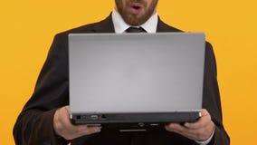 Человек смотрит удивленным читающ последние новости на ноутбуке, свободном wifi, конце-вверх видеоматериал