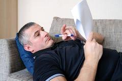 Человек смотрит через деловые документы, отчеты Беспокойство, работа в домашнем окружении стоковая фотография