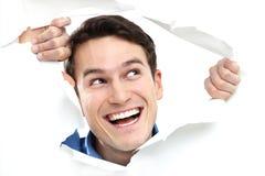 Человек смотрря прищурясь через отверстие на бумаге стоковое изображение