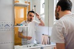 Человек смотря себя в зеркале в bathroom Он расчесывает его волосы стоковое изображение rf