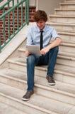 Человек смотря франтовскую таблетку сидя на лестницах Стоковое фото RF