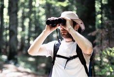 Человек смотря через бинокли Стоковое Фото