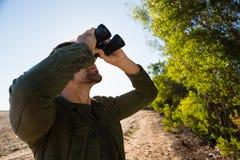 Человек смотря через бинокулярное на поле Стоковые Фото