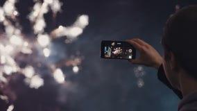 Человек снимает видео selfie праздничной pyrotechnic выставки в городе ночи акции видеоматериалы