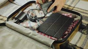 Человек собирает вещи на дороге, кладет портмоне с деньгами в его чемодан акции видеоматериалы