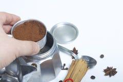 Человек собирает кофеварку гейзера, заполняющ его с водой и кофе Рядом на лож таблицы зерна кофе и специй: c Стоковые Изображения