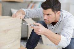 Человек собирает шкаф мебели стоковое изображение rf