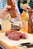 Человек солит мясо Стоковое Изображение RF