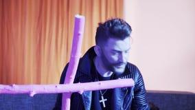 Человек со стильной стрижкой в кожаной куртке поет и танцует держащ розовый крест сток-видео