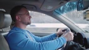 Человек спокойно управляет автомобилем на шоссе видеоматериал