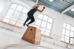 Человек спорта нося в sportswear выполняет скачки коробки на спортзале стоковое изображение rf
