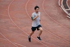 Человек спортсмена азиатский бежать на беговой дорожке в стадионе Здоровая активная концепция образа жизни Стоковое Фото