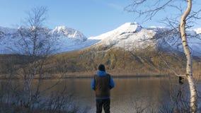 Человек, средн-постаретый спортсмен, встречает рассвет в горах Он восхищает отражение солнца и гор внутри акции видеоматериалы