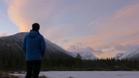 Человек, средн-постаретый спортсмен, встречает рассвет в горах Он восхищает отражение солнца и гор внутри сток-видео