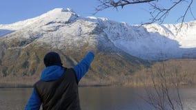 Человек, средн-постаретый спортсмен, встречает рассвет в горах Он поднимает его руки вверх, радуется на новом дне все акции видеоматериалы