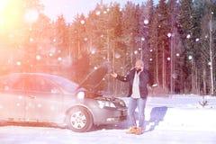 Человек стоит внешний близко сломанный автомобиль стоковое фото
