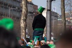 Человек стоит над толпами в шляпе стиля Ирландского и зеленых одеждах в Дублине, Ирландии на день ` s St. Patrick стоковые изображения rf