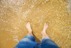 Человек стоит на морской воде стоковые изображения
