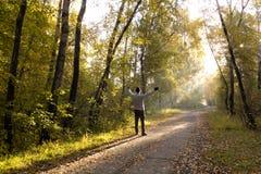 Человек стоит на пути посыпанном с желтой листвой, и протягивает стоковая фотография rf