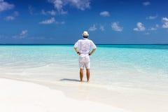Человек стоит на тропическом пляже и наслаждается его летом стоковая фотография rf