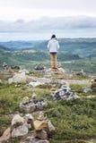 Человек стоит на холме среди камней стоковое фото rf