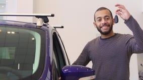 Человек стоит около фиолетового кроссовера на выставочном зале стоковое фото rf