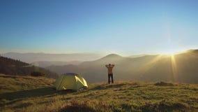 Человек стоит около шатра в горах сток-видео