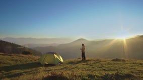 Человек стоит около шатра в горах акции видеоматериалы