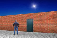Человек стоит перед длинной кирпичной стеной с закрытой дверью Стоковые Изображения