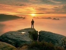 Человек стоит самостоятельно на пике утеса Hiker наблюдая к осени Солнцю на горизонте Красивый момент чудо природы цветасто стоковое изображение