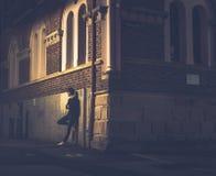 Человек стоя близко угол здания на улице стоковые изображения