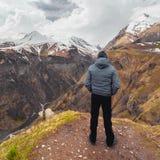 Человек стоя на заднем плане гор, Georgia Стоковое Изображение