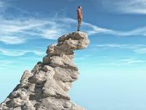 Человек стоя на каменной скале стоковое изображение rf