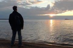 Человек стоя на речном береге на заходе солнца Стоковое Изображение