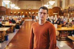 Человек студента Intelegent в стеклах стоит публично читальный зал библиотеки стоковые фото