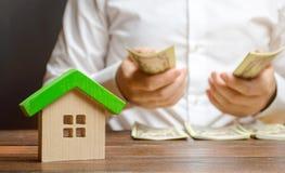 Человек считает деньги на предпосылке диаграмм дома Вычисление налога на собственность, оплаты общих назначений Считать стоковое фото rf