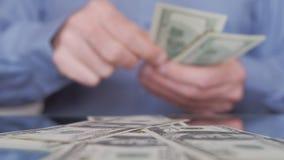 Человек считая долларовые банкноты и падая они на таблице сток-видео