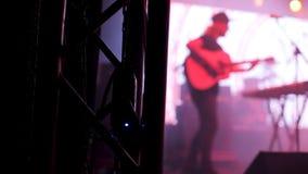 Человек с акустической гитарой выполняя на этапе концерта рок-музыки страны видеоматериал