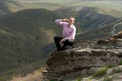 Человек с блокнотом и телефоном на горе Стоковые Фотографии RF
