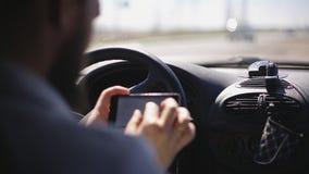 Человек с бородой вымощает трассу на smartphone пока сидящ в автомобиле акции видеоматериалы