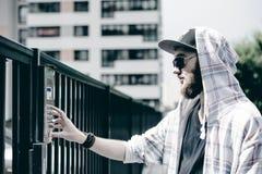 человек с бородой в светлой checkered куртке с клобуком в крышке и солнечных очках комплектует вверх номер квартиры на кнопочной  стоковые изображения rf