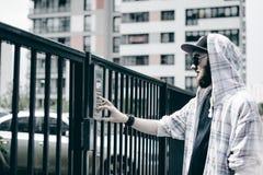 человек с бородой в светлой checkered куртке с клобуком в крышке и солнечных очках комплектует вверх номер квартиры на кнопочной  стоковое фото
